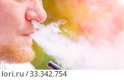 Купить «A young man relaxes in nature and releases smoke while smoking a hookah.», фото № 33342754, снято 22 июня 2019 г. (c) Акиньшин Владимир / Фотобанк Лори