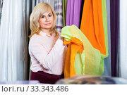 Купить «Mature woman seller showing curtain in the curtains shop», фото № 33343486, снято 17 января 2018 г. (c) Яков Филимонов / Фотобанк Лори
