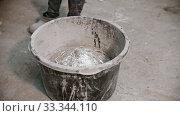 Купить «Concrete industry - worker in gloves about to mix the concrete - adding pieces of glass in the mix», видеоролик № 33344110, снято 5 июня 2020 г. (c) Константин Шишкин / Фотобанк Лори