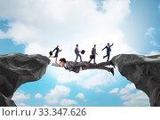 Купить «Businessman acting as a bridge in support concept», фото № 33347626, снято 3 апреля 2020 г. (c) Elnur / Фотобанк Лори
