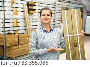 Купить «Woman choosing wooden panels at gardening store», фото № 33355086, снято 3 июня 2020 г. (c) Яков Филимонов / Фотобанк Лори