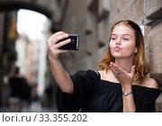Купить «positive female making selfie in the city center», фото № 33355202, снято 4 апреля 2020 г. (c) Яков Филимонов / Фотобанк Лори
