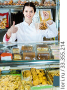 Купить «Young woman selling cookies and other fillings», фото № 33355214, снято 22 марта 2017 г. (c) Яков Филимонов / Фотобанк Лори