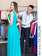 Купить «Family couple choosing dress in shop», фото № 33355246, снято 11 апреля 2017 г. (c) Яков Филимонов / Фотобанк Лори