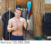 Купить «Athletic man standing near hangar with surf equipment», фото № 33355334, снято 30 апреля 2018 г. (c) Яков Филимонов / Фотобанк Лори