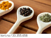 Купить «spoons with different spices on wooden table», фото № 33355658, снято 6 сентября 2018 г. (c) Syda Productions / Фотобанк Лори