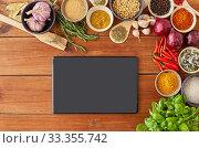 Купить «tablet pc computer among spices on wooden table», фото № 33355742, снято 6 сентября 2018 г. (c) Syda Productions / Фотобанк Лори