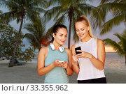 Купить «women or female friends with smartphones on beach», фото № 33355962, снято 28 июля 2019 г. (c) Syda Productions / Фотобанк Лори