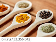 Купить «spoons with different spices on wooden table», фото № 33356042, снято 6 сентября 2018 г. (c) Syda Productions / Фотобанк Лори