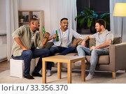 Купить «happy male friends drinking beer at home at night», фото № 33356370, снято 28 декабря 2019 г. (c) Syda Productions / Фотобанк Лори