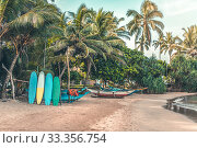 Surfboards resting on a wooden stand in the sand at a surf station in Sri Lanka Hikkaduwa (2019 год). Стоковое фото, фотограф katalinks / Фотобанк Лори