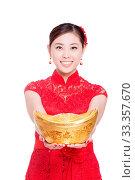 Купить «Young asian woman in red cheongsam holds gold ingot in chinese new year», фото № 33357670, снято 14 июля 2020 г. (c) age Fotostock / Фотобанк Лори