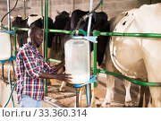 Portrait of farmer man staning near cow milking machines indoor at farm. Стоковое фото, фотограф Яков Филимонов / Фотобанк Лори