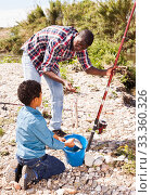 Boy and his father holding fish on hook. Стоковое фото, фотограф Яков Филимонов / Фотобанк Лори