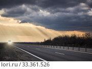 Купить «Truck rides on an asphalt road in the background of thunderclouds and rays of the sun», фото № 33361526, снято 18 марта 2019 г. (c) Олег Белов / Фотобанк Лори