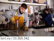 Купить «Confident man mechanic drilling metal sheet in workshop», фото № 33365342, снято 4 августа 2020 г. (c) Яков Филимонов / Фотобанк Лори