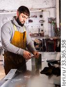 Купить «Young man engineer calculation size of material», фото № 33365358, снято 4 апреля 2020 г. (c) Яков Филимонов / Фотобанк Лори