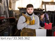 Купить «Man mechanic working with hand hammer in workshop», фото № 33365362, снято 4 февраля 2020 г. (c) Яков Филимонов / Фотобанк Лори