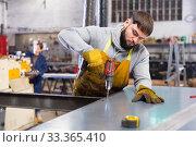Man engineer drilling metal sheet in workshop. Стоковое фото, фотограф Яков Филимонов / Фотобанк Лори