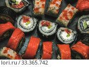 Купить «Various kinds of sushi served on dark plate macro», фото № 33365742, снято 11 марта 2020 г. (c) katalinks / Фотобанк Лори