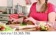 Купить «A young adult woman is preparing a vegetable salad sitting at a table in the kitchen», видеоролик № 33365786, снято 11 марта 2020 г. (c) Алексей Кузнецов / Фотобанк Лори
