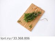 Купить «bunch of rosemary on wooden cutting board», фото № 33368806, снято 12 июля 2018 г. (c) Syda Productions / Фотобанк Лори