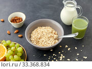 oatmeal with fruits, almond nuts and jug of milk. Стоковое фото, фотограф Syda Productions / Фотобанк Лори
