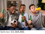 friends or soccer fans with ball and beer at home. Стоковое фото, фотограф Syda Productions / Фотобанк Лори