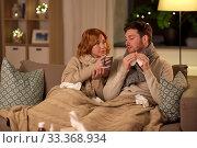 Купить «sick young couple drinking hot tea at home», фото № 33368934, снято 6 февраля 2020 г. (c) Syda Productions / Фотобанк Лори
