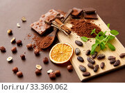 Купить «chocolate with hazelnuts, cocoa beans and powder», фото № 33369062, снято 1 февраля 2019 г. (c) Syda Productions / Фотобанк Лори