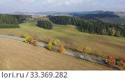 Купить «Scenic aerial view of picturesque autumn countryside landscape with straight road between yellow trees», видеоролик № 33369282, снято 15 октября 2019 г. (c) Яков Филимонов / Фотобанк Лори