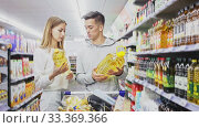 Portrait of friendly man and woman with shopping cart choosing olive oil in supermarket. Стоковое видео, видеограф Яков Филимонов / Фотобанк Лори