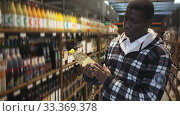 Купить «Focused African American man making purchases in store, choosing vegetable oil», видеоролик № 33369378, снято 30 июня 2020 г. (c) Яков Филимонов / Фотобанк Лори