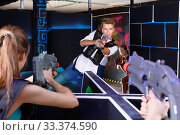 Купить «Two laser tag teams playing enthusiastically and aiming at each other in dark room», фото № 33374590, снято 27 августа 2018 г. (c) Яков Филимонов / Фотобанк Лори