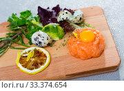 Купить «Salmon tartar with balsamic, greens, lemon, quail egg on wooden desk», фото № 33374654, снято 5 июня 2020 г. (c) Яков Филимонов / Фотобанк Лори