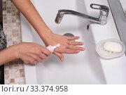 Девушка наносит крем на кожу рук в ванной комнате. Стоковое фото, фотограф Иванов Алексей / Фотобанк Лори