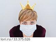Купить «Woman wearing a crown on her head and protective face mask looking at camera», фото № 33375026, снято 15 марта 2020 г. (c) Kira_Yan / Фотобанк Лори