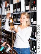 Купить «Attentive woman looking for perfect wine», фото № 33375666, снято 31 марта 2020 г. (c) Яков Филимонов / Фотобанк Лори