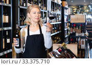 Focused mature woman wine producer inspecting quality of wine in wineshop on background with shelves of wine bottles. Стоковое фото, фотограф Яков Филимонов / Фотобанк Лори