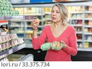 Купить «Mature woman choosing fresh eggs in grocery shop», фото № 33375734, снято 8 февраля 2019 г. (c) Яков Филимонов / Фотобанк Лори