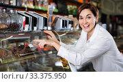 Купить «Female customer examining desserts in confectionery», фото № 33375950, снято 24 января 2017 г. (c) Яков Филимонов / Фотобанк Лори