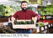 Купить «Positive man seller showing zucchinis in shop», фото № 33375962, снято 15 ноября 2016 г. (c) Яков Филимонов / Фотобанк Лори