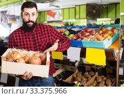 Купить «Young male seller offering pomegranates in shop», фото № 33375966, снято 15 ноября 2016 г. (c) Яков Филимонов / Фотобанк Лори