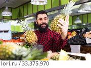 Купить «man seller showing pineapples», фото № 33375970, снято 15 ноября 2016 г. (c) Яков Филимонов / Фотобанк Лори