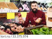 Купить «Male seller offering onions», фото № 33375974, снято 15 ноября 2016 г. (c) Яков Филимонов / Фотобанк Лори