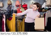 Купить «Smiling female deciding on pretty blouse», фото № 33375990, снято 7 февраля 2017 г. (c) Яков Филимонов / Фотобанк Лори