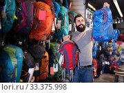 Купить «Smiling man customer examining rucksacks in store», фото № 33375998, снято 24 февраля 2017 г. (c) Яков Филимонов / Фотобанк Лори