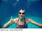 Купить «Female swimmer shows thumbs up underwater in pool», фото № 33376070, снято 19 февраля 2020 г. (c) Tryapitsyn Sergiy / Фотобанк Лори