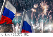 Russia flag waving in the wind and fireworks in honor of Victory Day celebration (WWII), Moscow, Russia. Three colors of Russian wavy flag as a patriotic symbol (2019 год). Стоковое фото, фотограф Владимир Журавлев / Фотобанк Лори