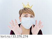 Купить «Woman wearing a crown on her head and protective face mask looking at camera», фото № 33376274, снято 15 марта 2020 г. (c) Kira_Yan / Фотобанк Лори